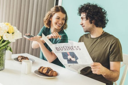 happy couple with smartphone and newspaper having breakfast together at home