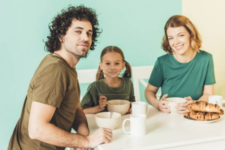 happy family eating breakfast together and smiling at camera