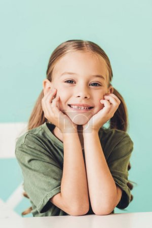 portrait of adorable little child sitting at table and smiling at camera