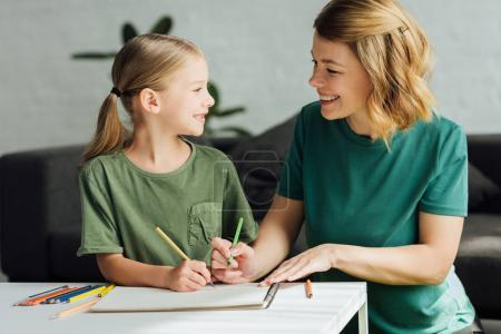 happy mother and daughter drawing together and smiling each other at home