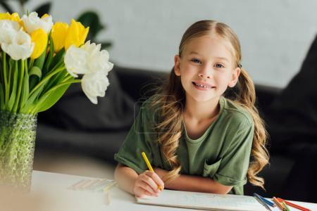 Photo for Portrait of cute little child drawing with colored pencils and smiling at camera at home - Royalty Free Image