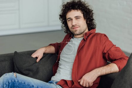 Photo for Portrait of handsome man with curly hair sitting on couch and looking at camera at home - Royalty Free Image