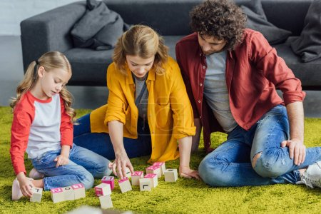 happy parents and cute little daughter playing with wooden blocks at home