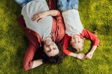 vue de dessus des heureux père et fille couché ensemble et souriant à la caméra