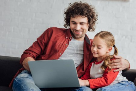 Photo for Happy father and daughter using laptop together at home - Royalty Free Image