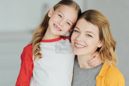 beautiful happy mother and daughter embracing and smiling at camera