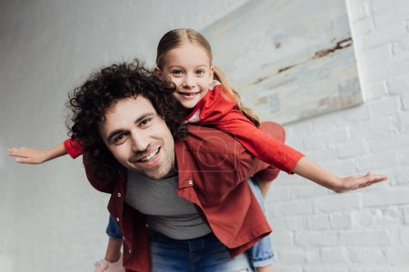 Photo for Happy father piggybacking cute little daughter and smiling at camera at home - Royalty Free Image