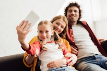 happy young family with one child taking selfie with smartphone