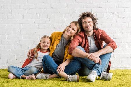 Photo pour Parents heureux avec la mignonne petite fille souriant à la caméra tout en siégeant ensemble - image libre de droit