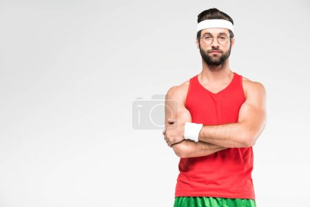 handsome sportsman posing in retro sportswear and sunglasses with crossed arms, isolated on white