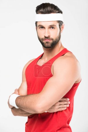 bearded sportsman in retro sportswear posing in crossed arms, isolated on white