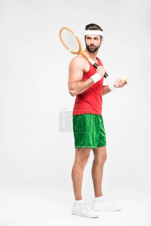 sportive tennis player posing with retro wooden racket and ball, isolated on white