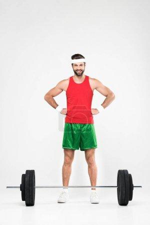 sportsman in retro sportswear standing near barbell, isolated on white