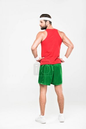 rear view of sportsman posing in retro sportswear, isolated on white