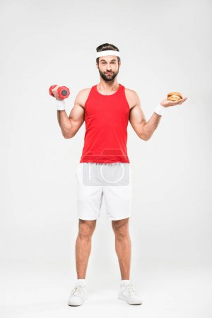 sportsman choosing fast food or healthy lifestyle, isolated on white