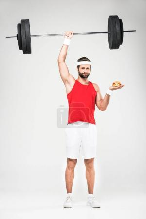 sportsman choosing hamburger or training with barbell, isolated on white