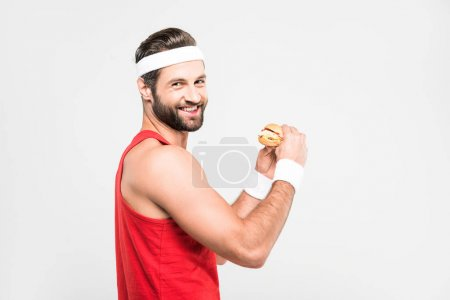 sportsman eating tasty hamburger, isolated on white
