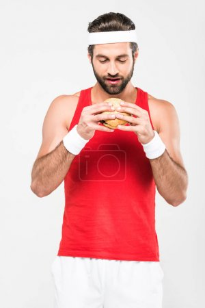 handsome sportsman eating fast food, isolated on white