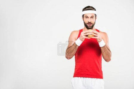 aufgeregter Sportler isst Hamburger, isoliert auf weiß
