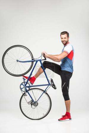 handsome smiling sportsman posing with bicycle, isolated on white