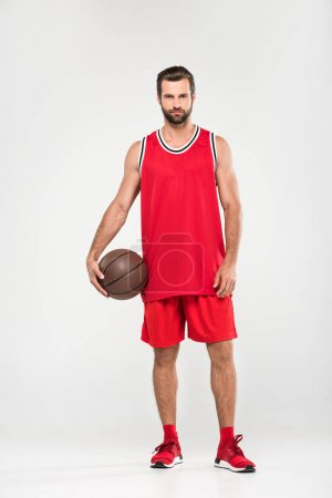 basketball player in red sportswear with ball, isolated on white
