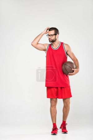 basketball player in red sportswear and retro glasses posing with ball, isolated on white