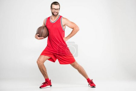 smiling basketball player in red sportswear and retro glasses posing with ball, isolated on white