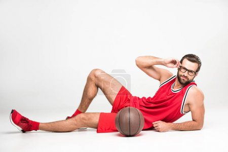 basketball player in red sportswear and glasses posing with ball, isolated on white