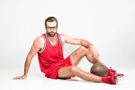 basketball player in red sportswear and eyeglasses sitting with ball, isolated on white