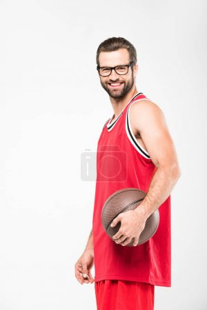 cheerful basketball player in retro glasses posing with ball, isolated on white
