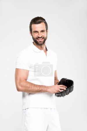 cheerful baseball player with baseball glove and ball, isolated on grey