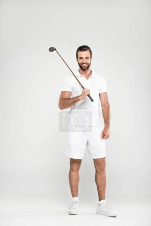 cheerful male golfer in white sportswear with golf club, isolated on grey
