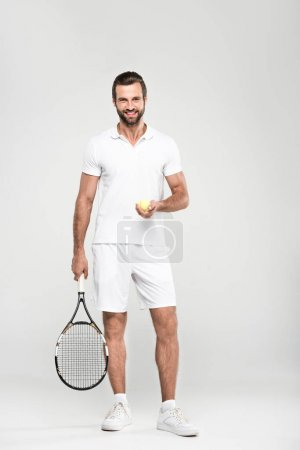 smiling tennis player with ball and racket, isolated on grey