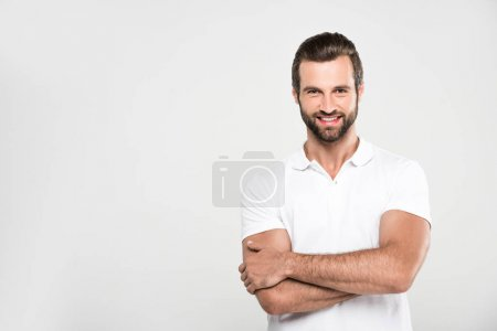 Photo for Handsome smiling man posing in white with crossed arms, isolated on grey - Royalty Free Image