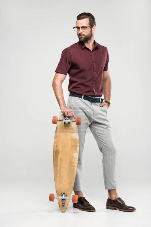 fashionable skater posing with longboard, isolated on grey