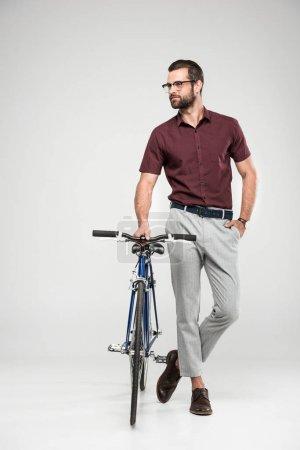 Photo pour Bel homme posant avec vélo, isolé sur fond gris - image libre de droit