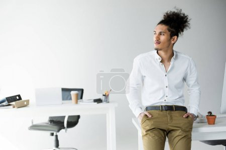 handsome young african american businessman with hands in pockets sitting on table and looking away in office