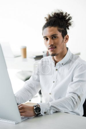 young african american businessman working with desktop computer and looking at camera