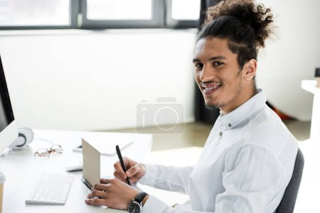 handsome young african american businessman smiling at camera while taking notes at workplace