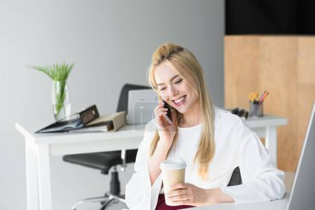 smiling young businesswoman holding disposable coffee cup and talking by smartphone in office