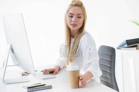 beautiful young businesswoman reaching for paper cup with coffee while using desktop computer at workplace