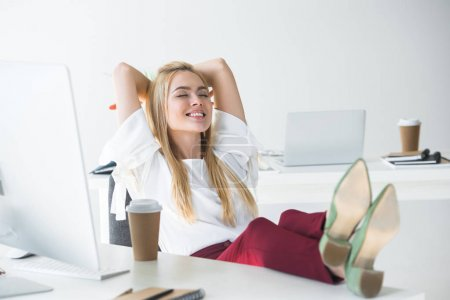 beautiful smiling young businesswoman with closed eyes sitting with hands behind head at workplace