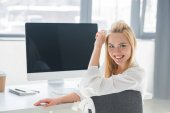 beautiful young blonde businesswoman smiling at camera while sitting at workplace