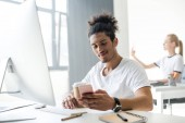smiling young african american man using smartphone while sitting at workplace