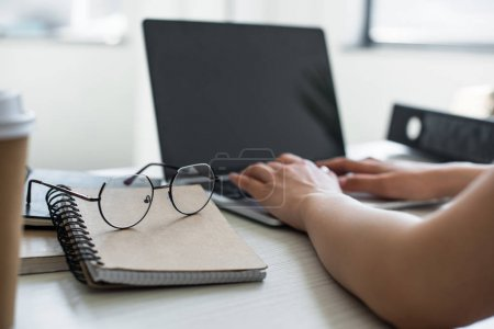 close-up view of spectacles on notepad and person using laptop behind