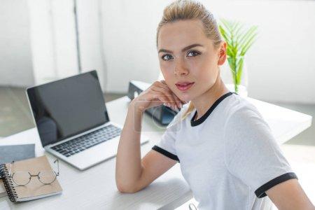 Photo pour Belle jeune femme regardant la caméra tout en travaillant avec un ordinateur portable au bureau - image libre de droit