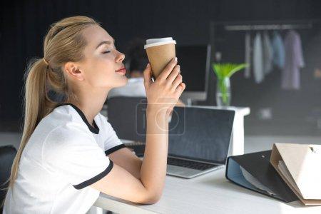 vue de côté de détendue jeune femme avec des yeux fermés, tenant la tasse de papier au bureau