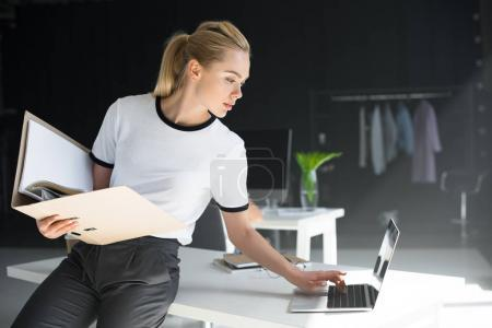 beautiful young woman holding folder and using laptop in office