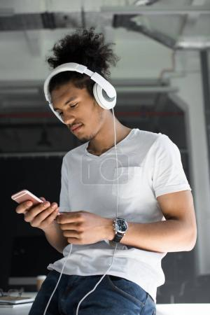 handsome young african american man in headphones using smartphone in office