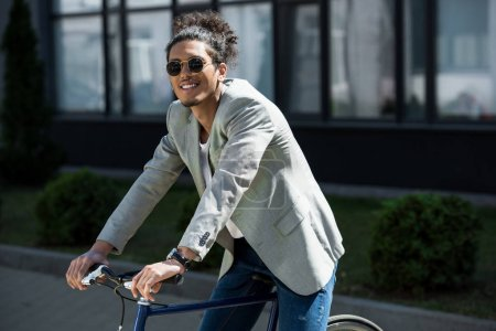 Photo for Stylish young african american man in sunglasses sitting on bicycle and smiling at camera - Royalty Free Image